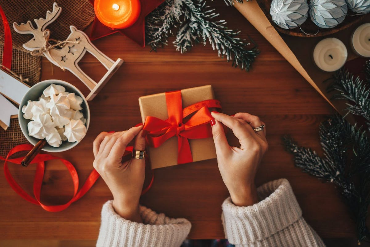 woman wrapping Christmas present with red bow