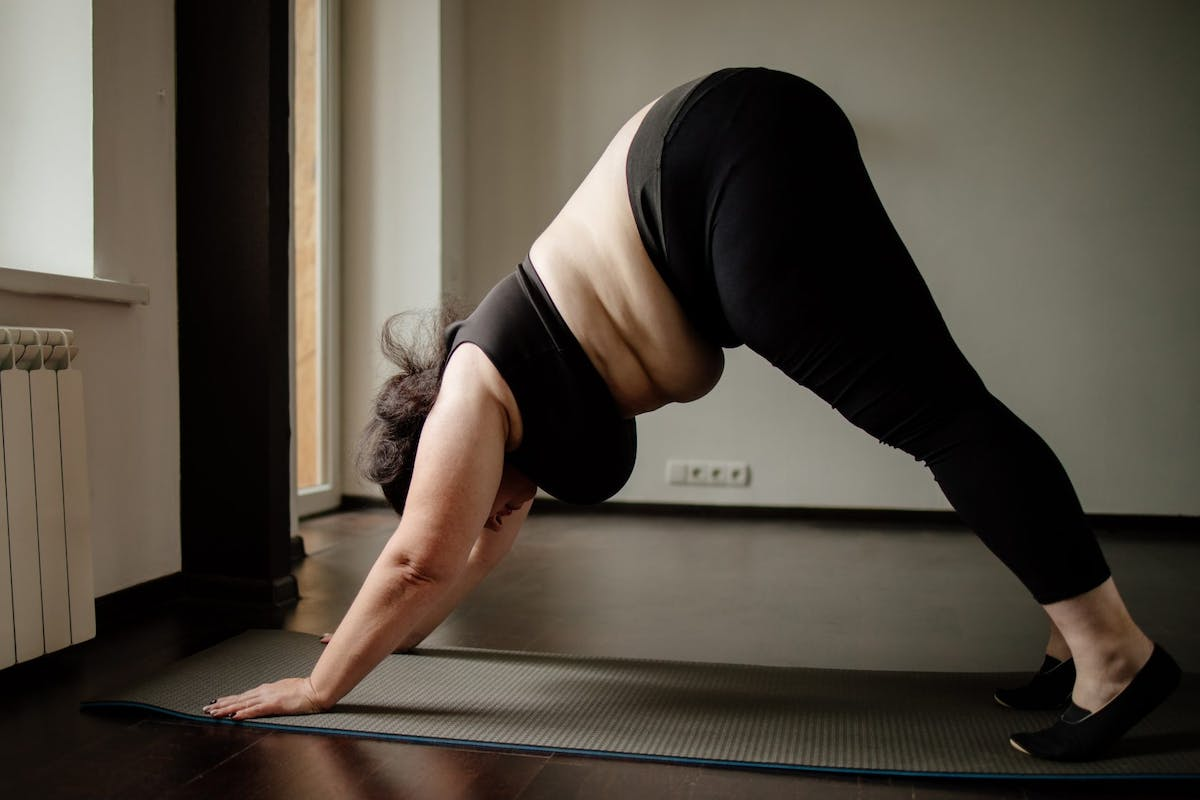 A woman in black activewear doing downward facing dog on a black yoga mat.