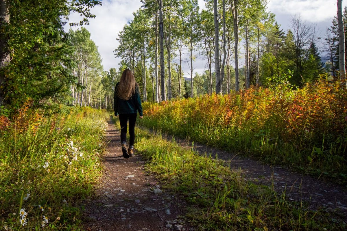 A woman walking through a wooded forest with long hair and leggings.