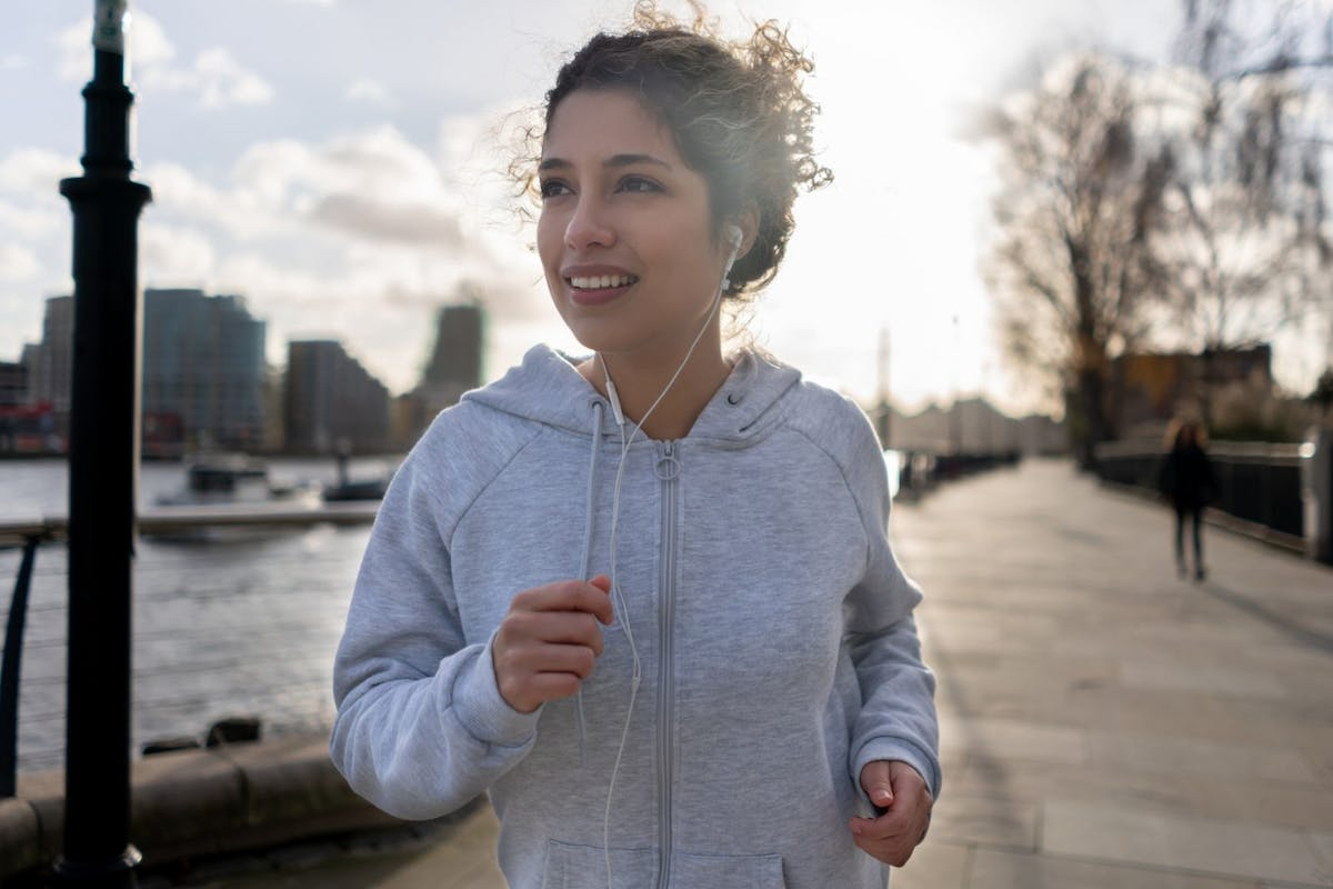 Woman smiling while running and wearing a grey hoodie