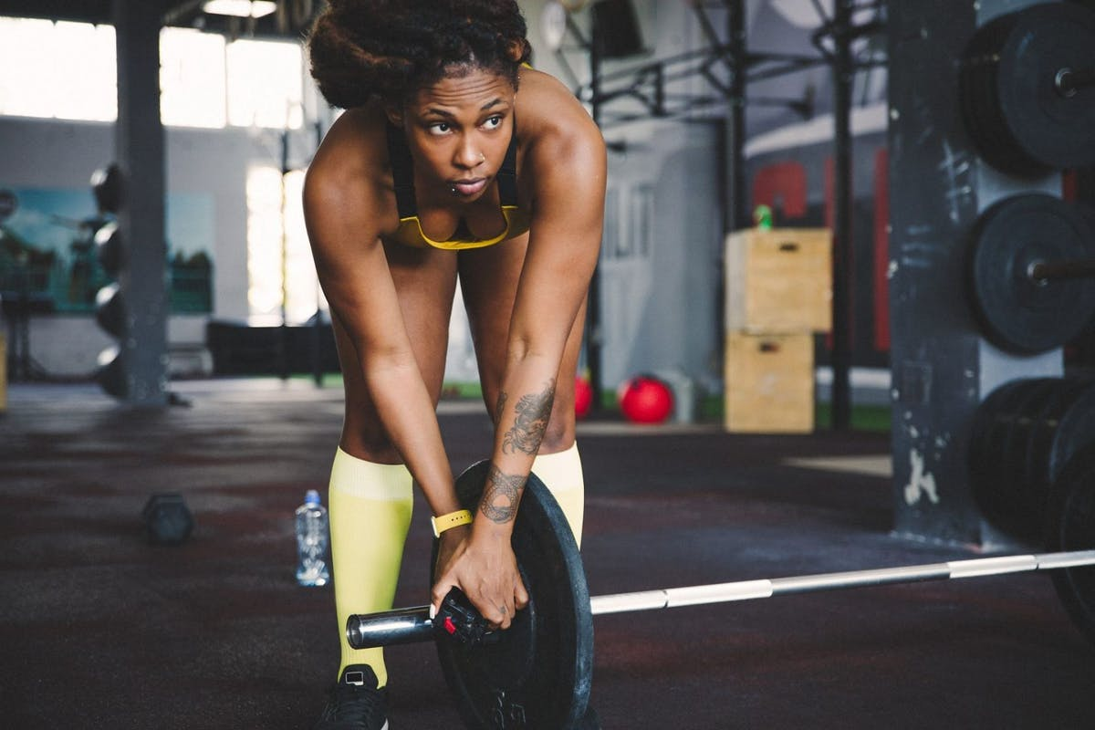 A woman places plates on a barbell in the gym before doing a deadlift