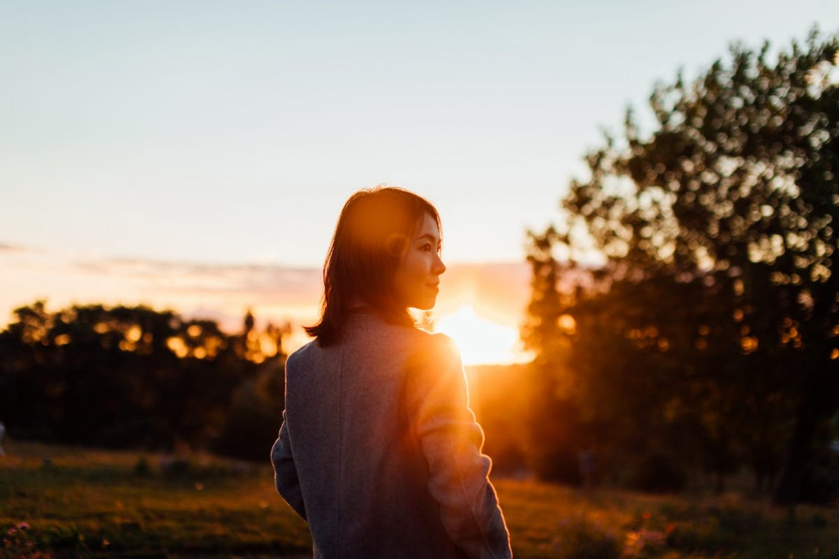 A side profile of a woman with the sun setting behind her