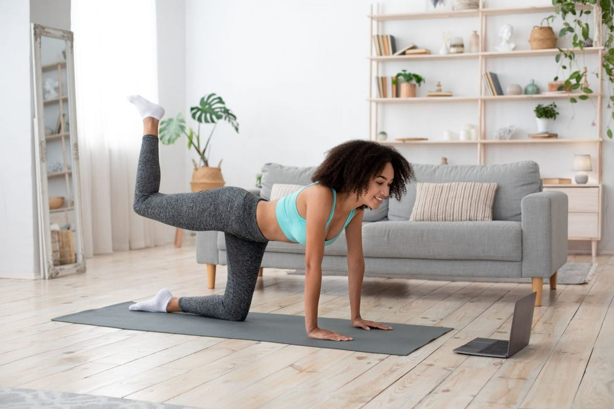 A woman doing a donkey kick exercise on a yoga mat at home.