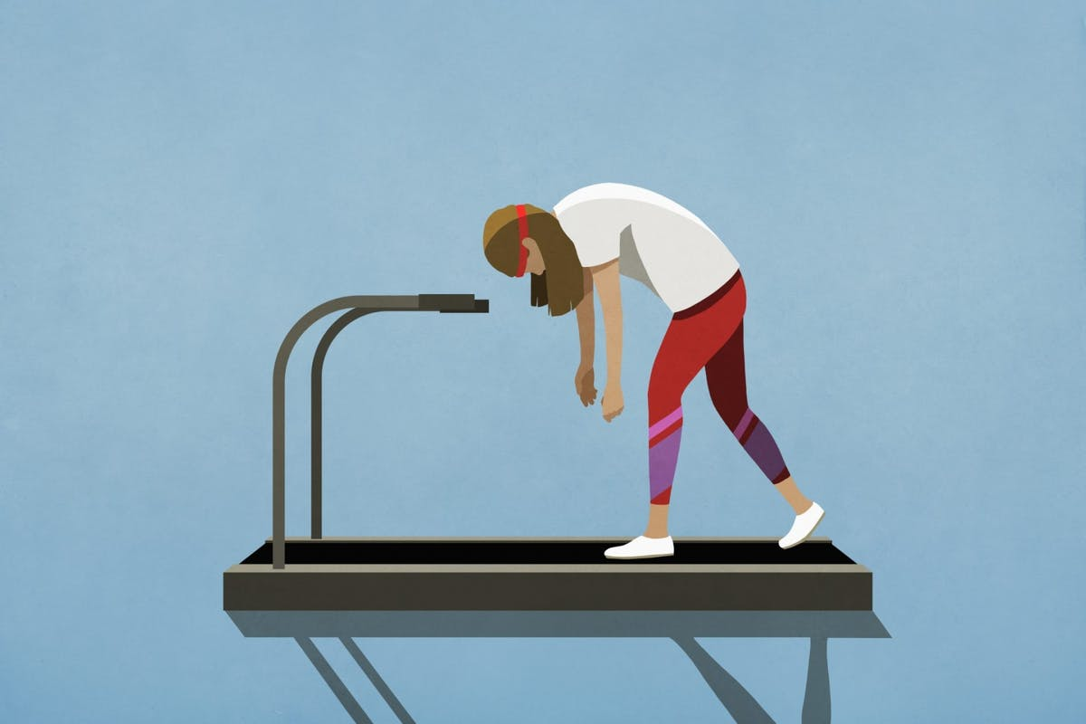 A woman exhausted on a treadmill