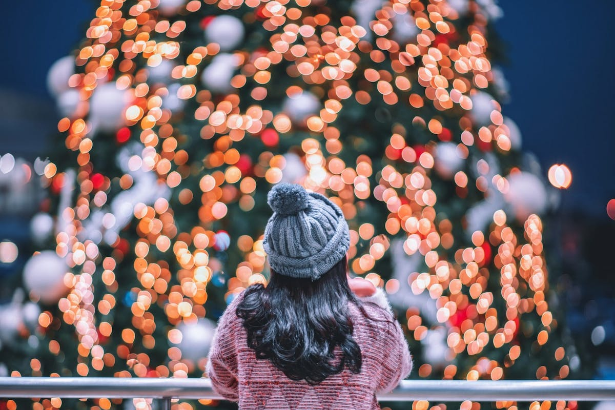 A woman looking at a christmas tree with lights