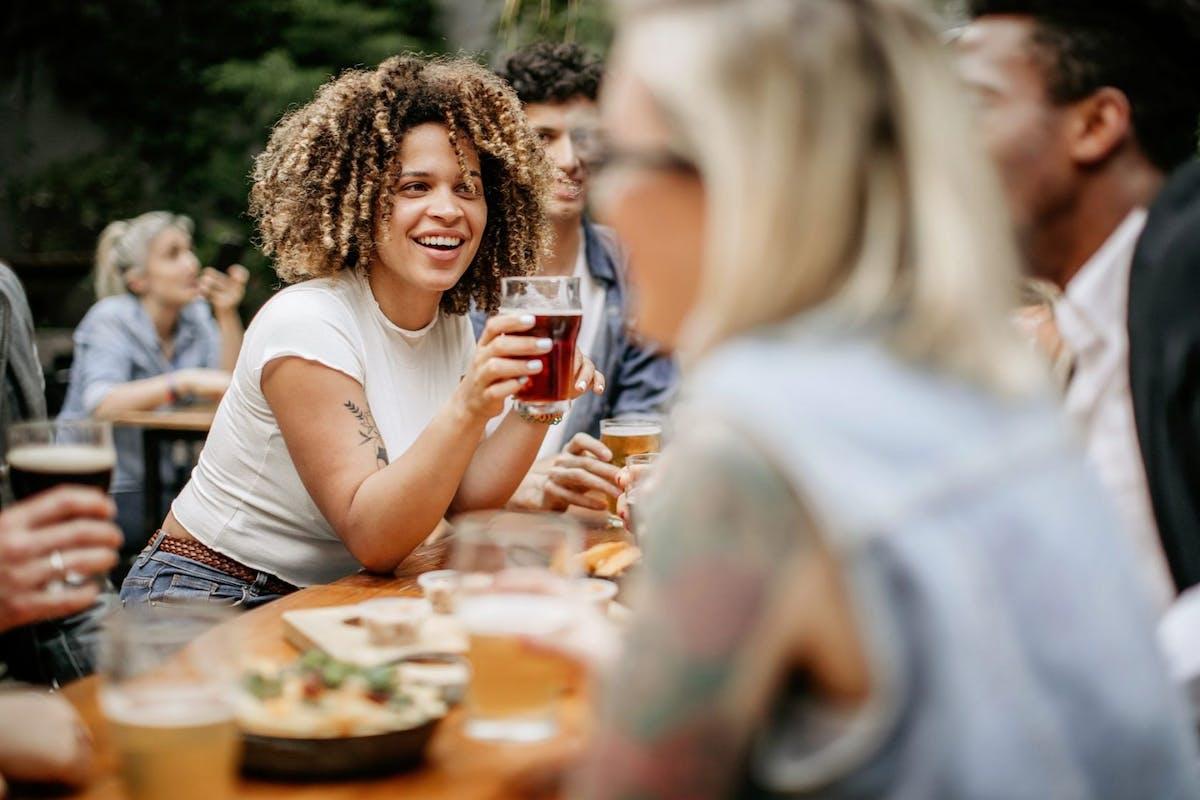 Women in a pub garden drinking beer in the sunshine.