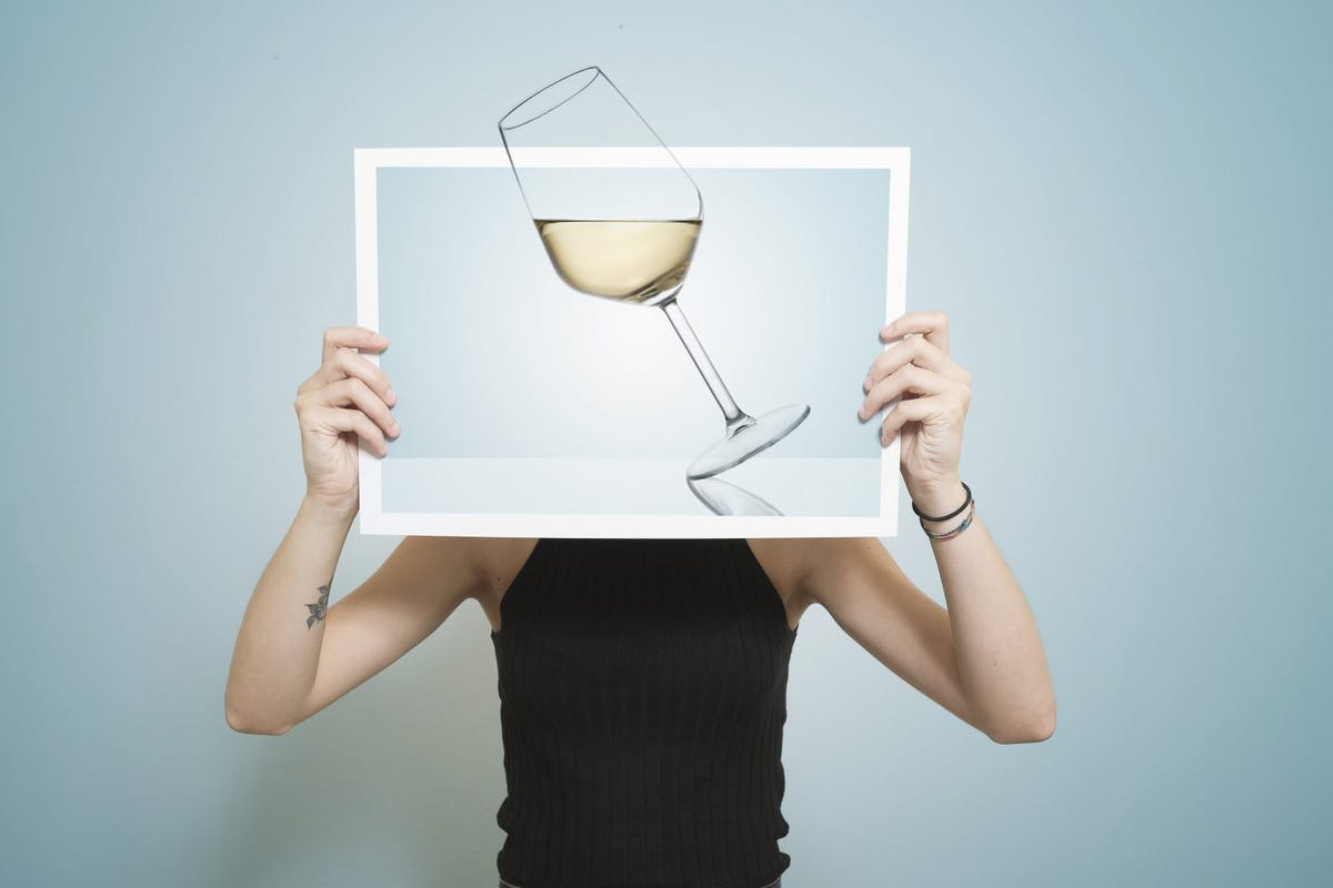 woman holding picture of glass of wine
