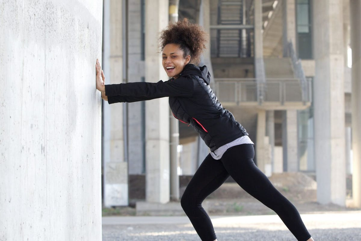 Woman stretching against a wall