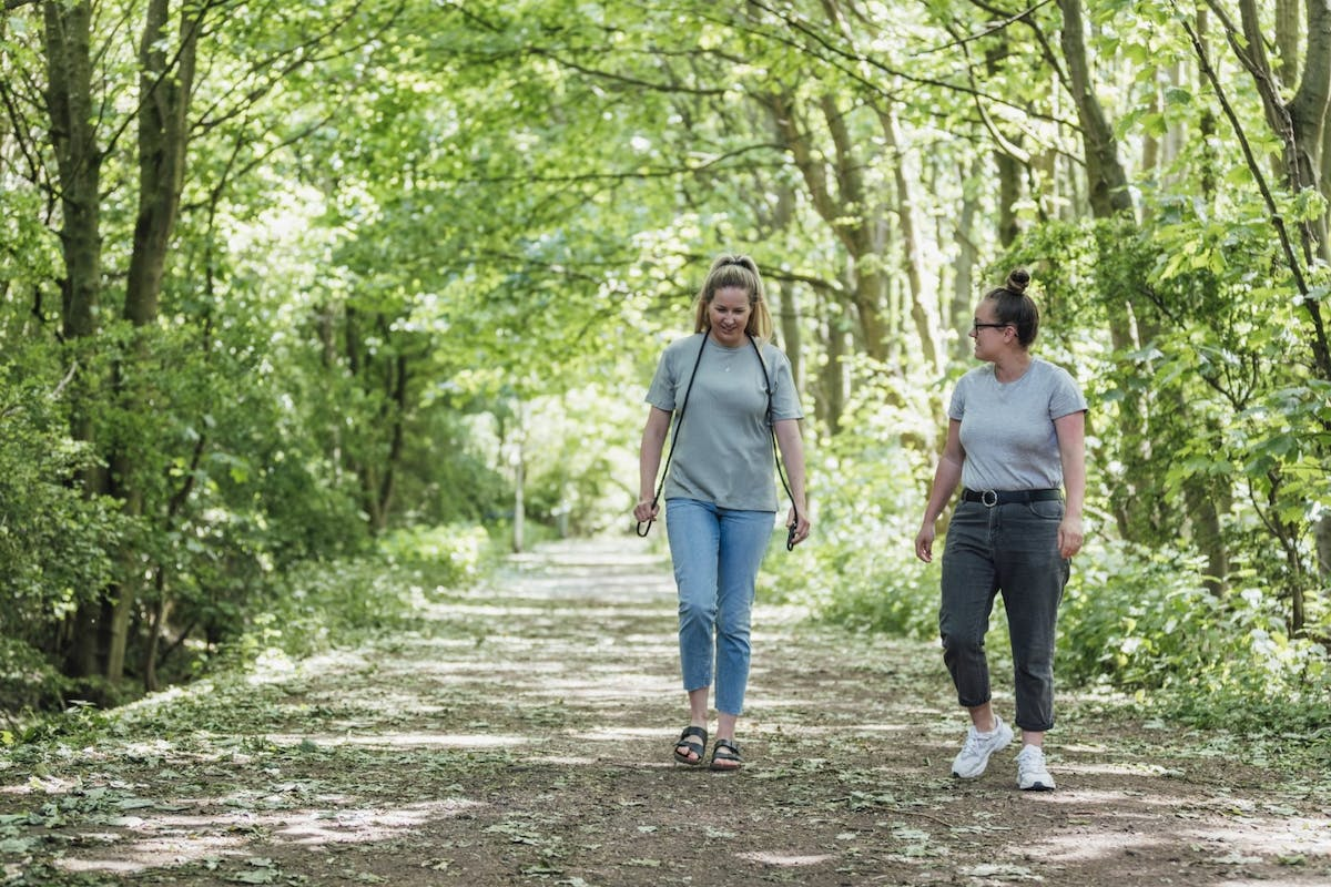 Two women walking outside in the woods during summer