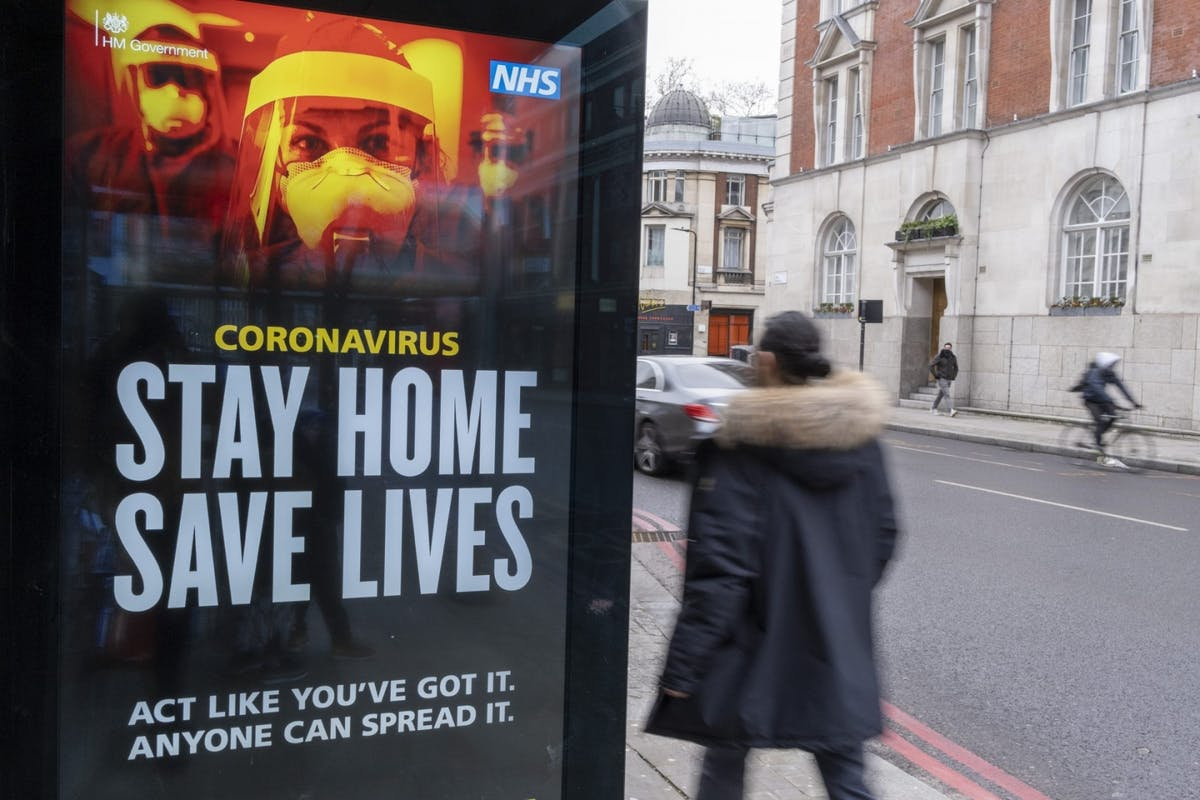 A woman walking past a 'stay home, save lives' sign in London