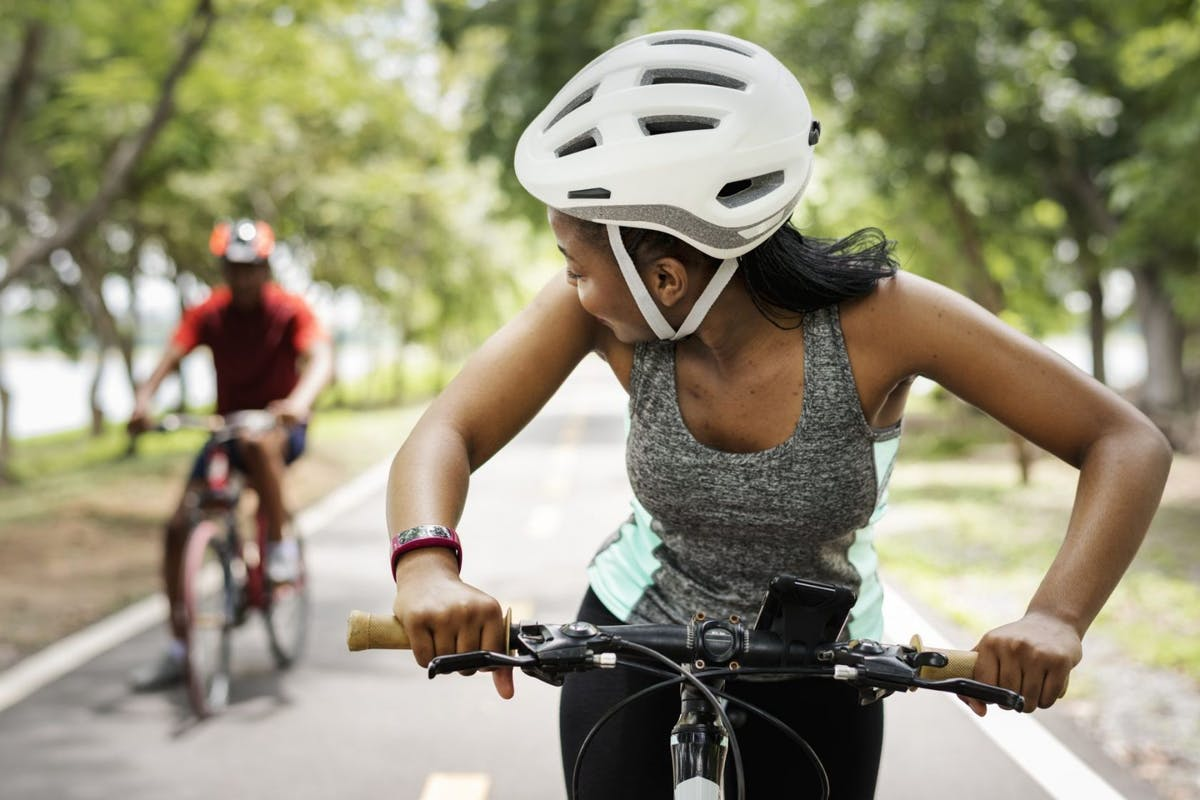 A woman cycling along a park path wearing a white helmet.