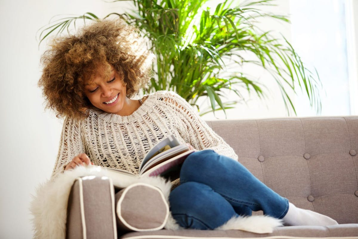 Woman curled up on the sofa in jeans and a jumper reading a book on her rest day from the gym.
