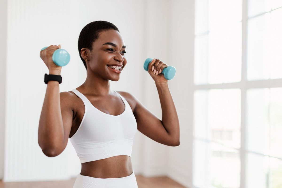 A woman lifting blue dumbbells in home workout