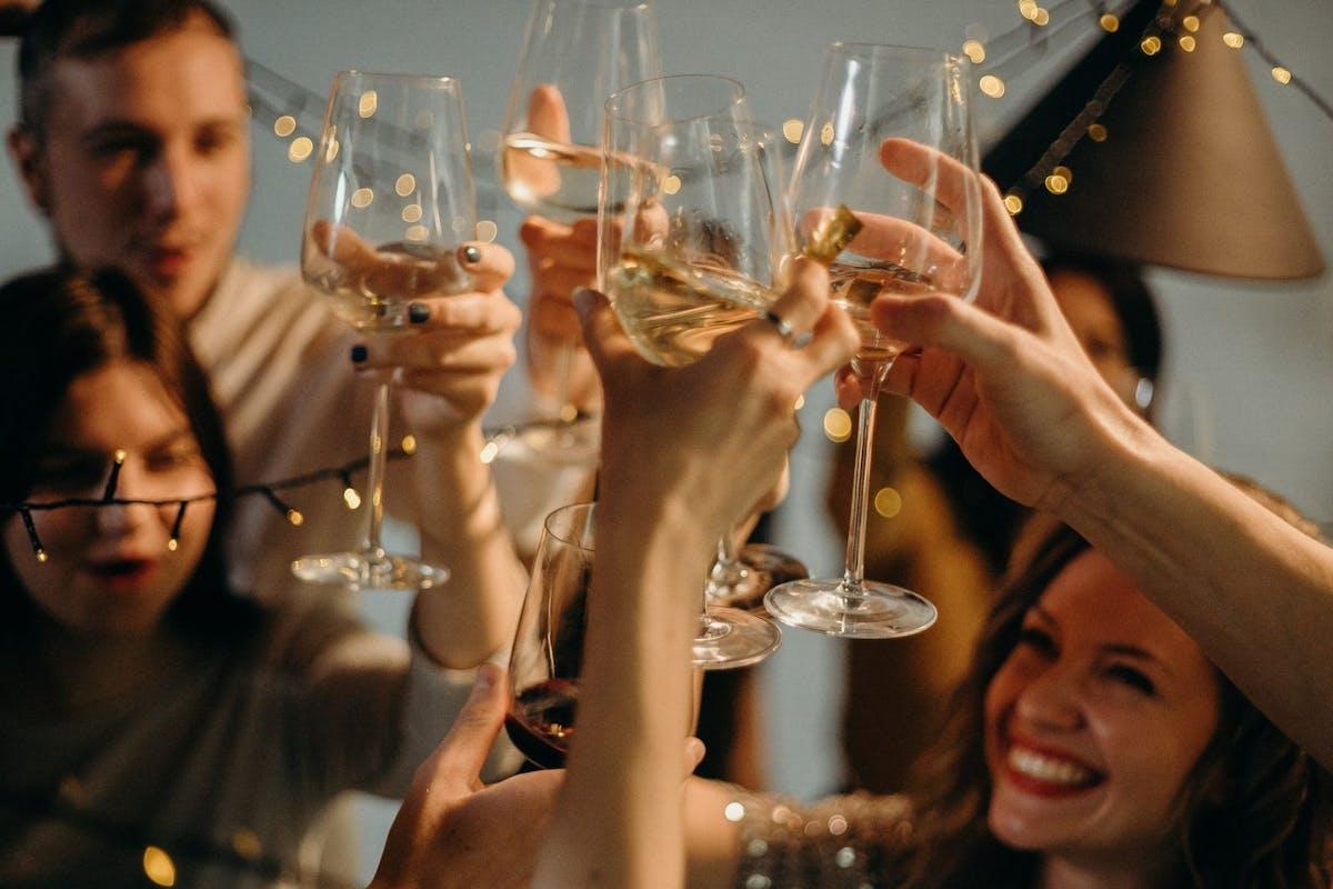 Friends cheersing wine glasses in a pub garden after lockdown.