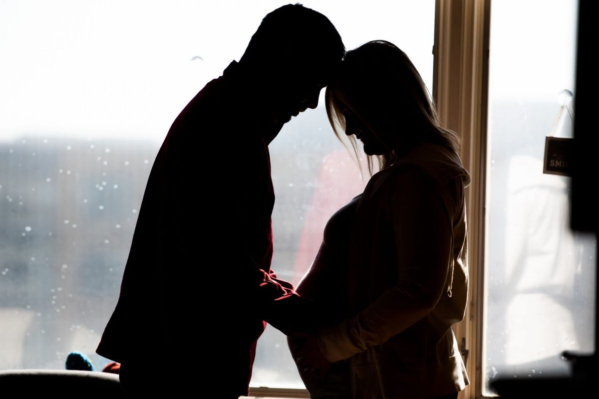 Pregnant Mother and Father of Twins in Hospital Room stand in silhouette shot - stock photo