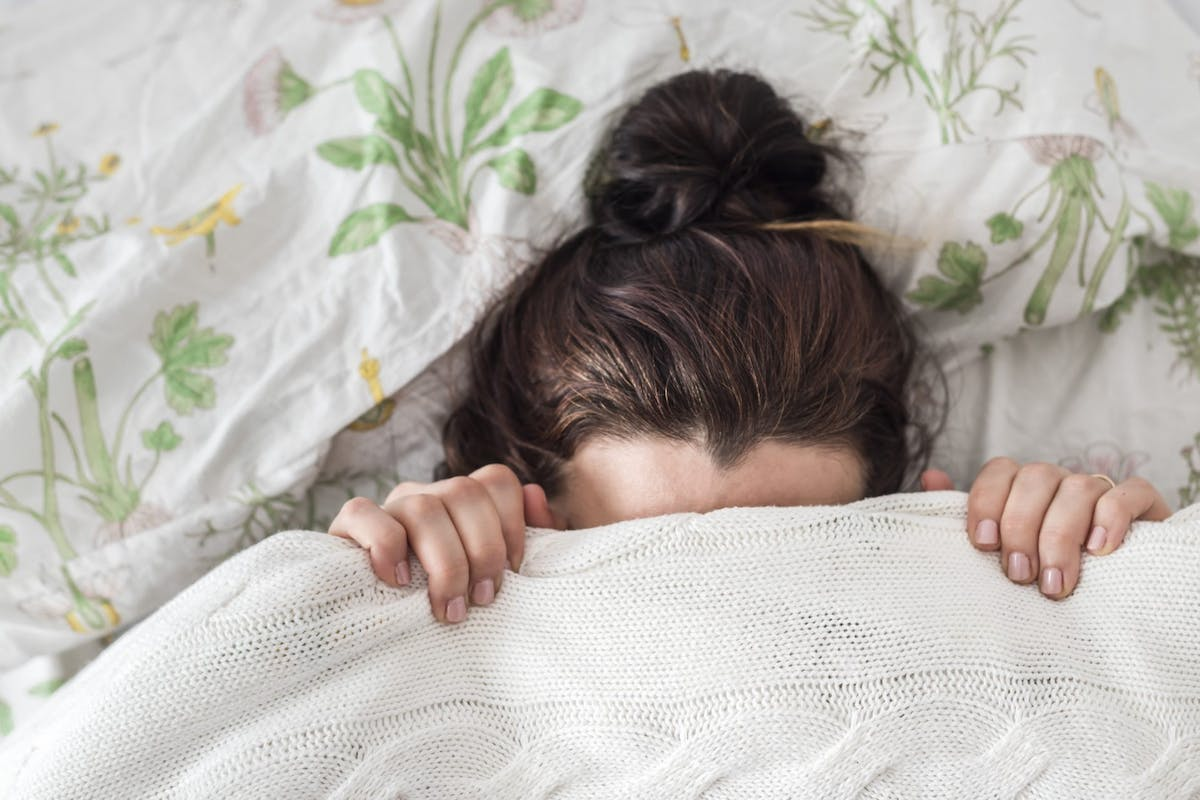 A woman hiding from the world under her duvet