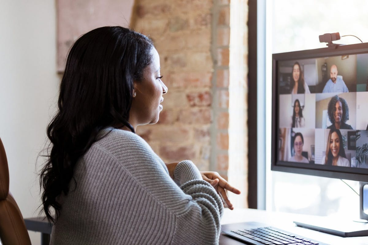A woman on a Zoom call with her colleagues while working from home