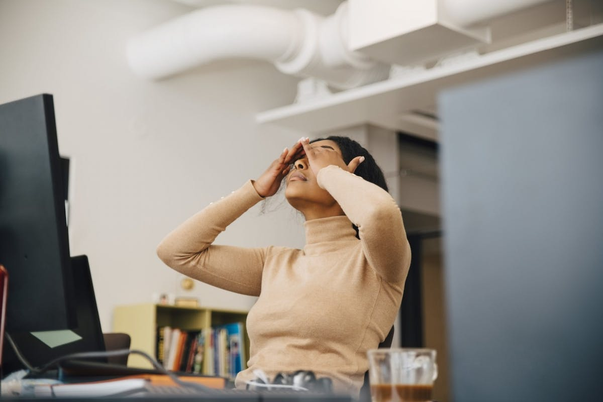 A woman losing concentration while working from home, holding her hands to her head