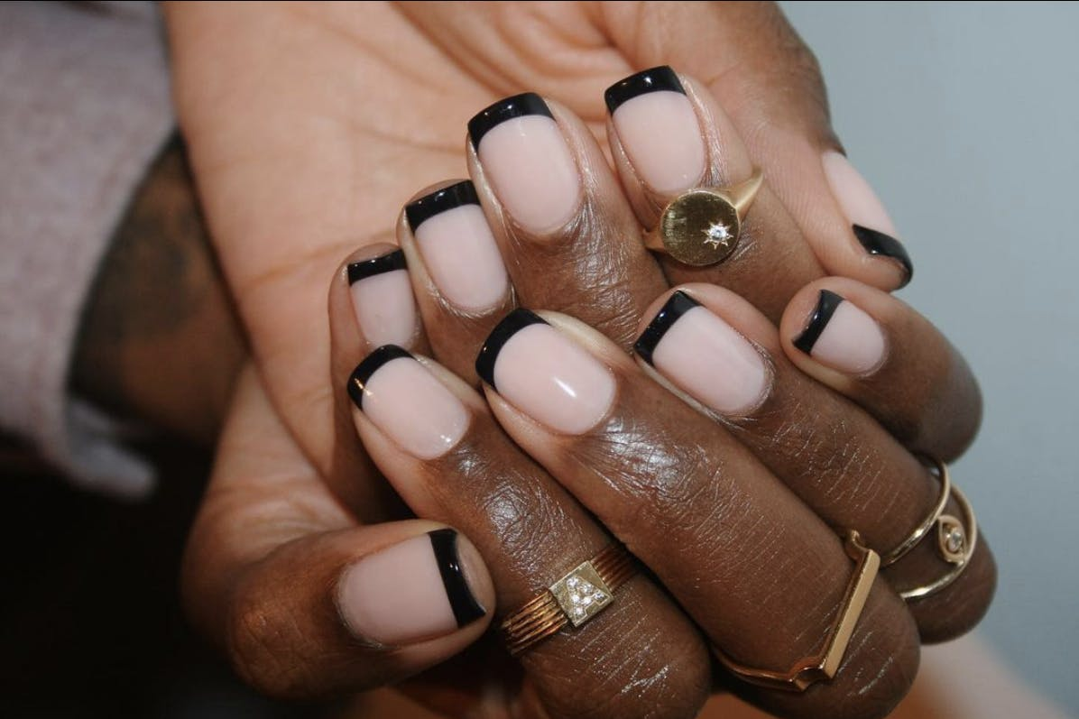 A woman's hand with a black-tipped French manicure