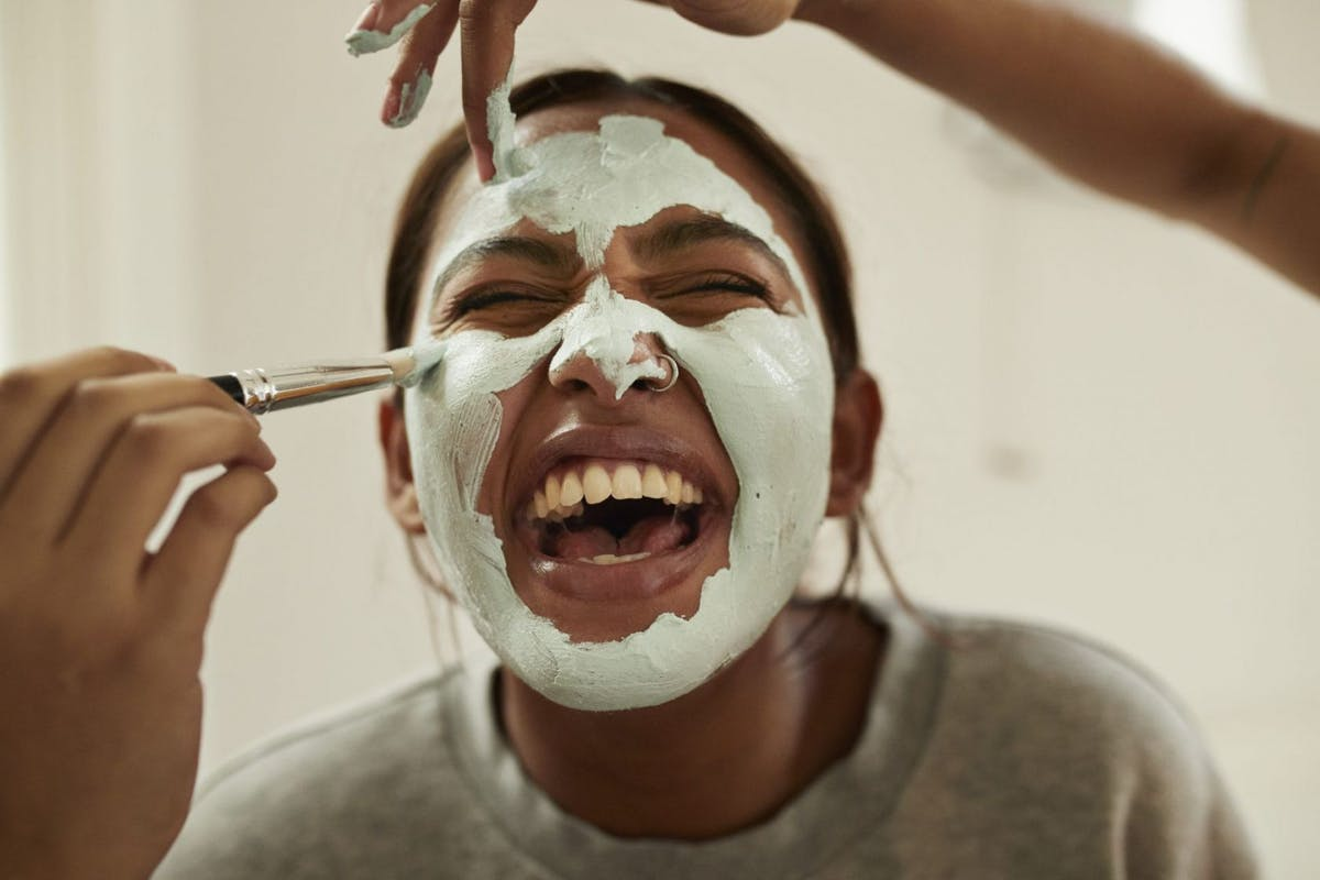 Woman laughing while her friends apply a green clay mask to her face