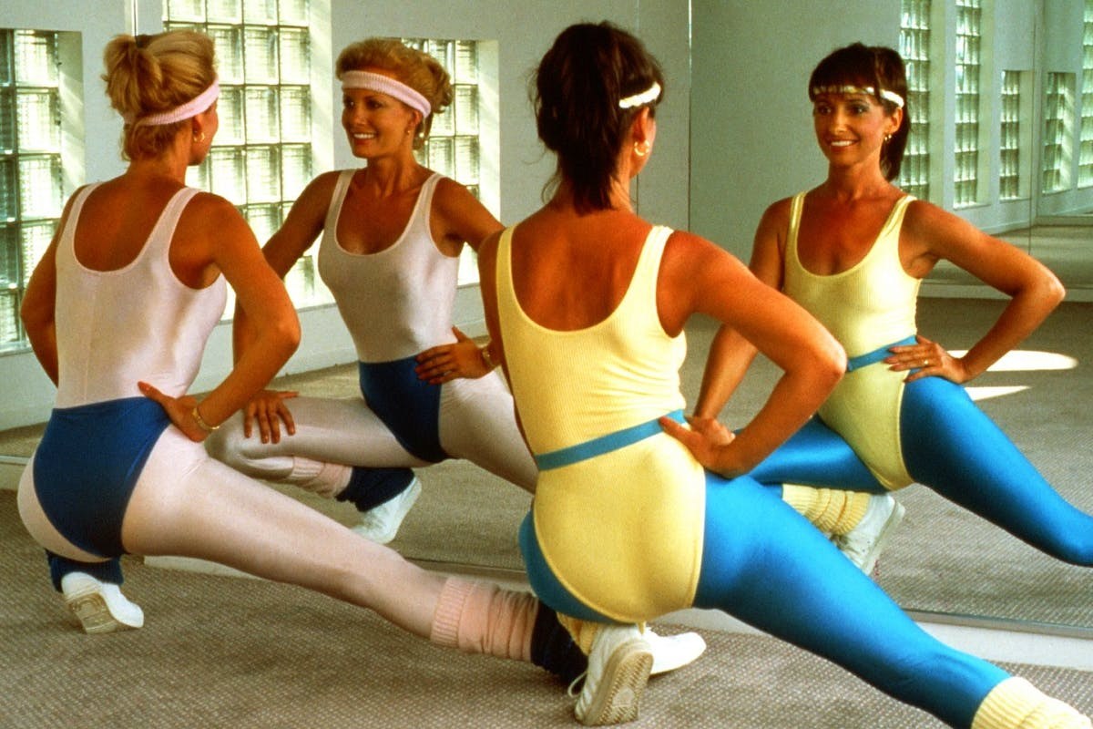 Two women doing 80s aerobics