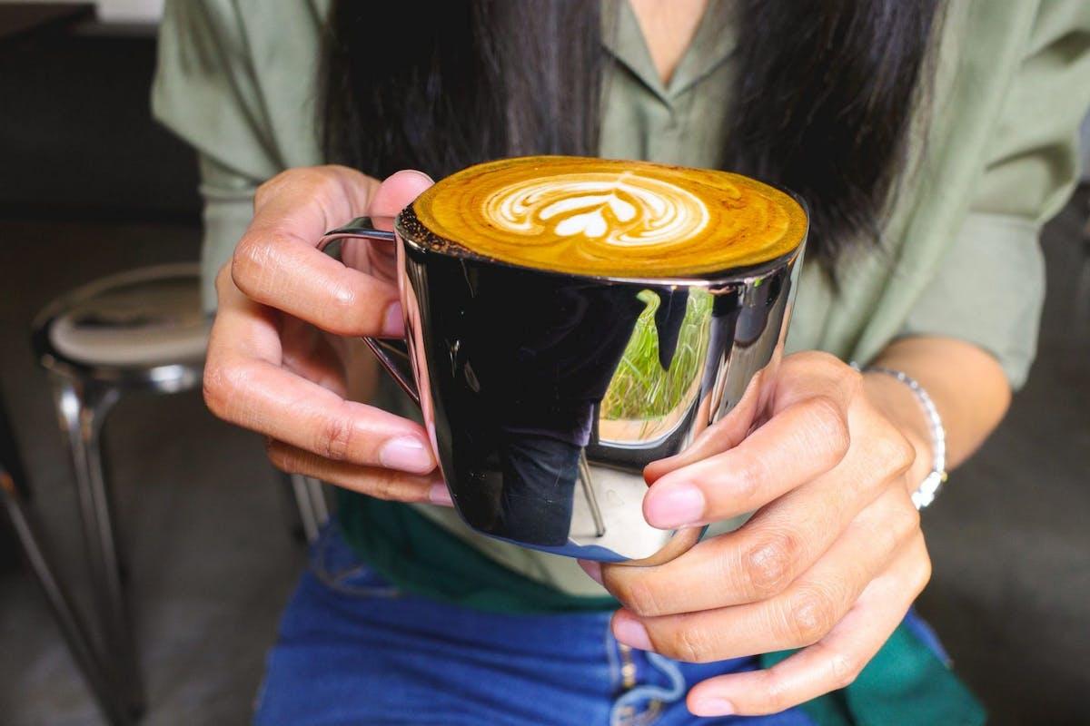 Woman holding a silver mug of coffee