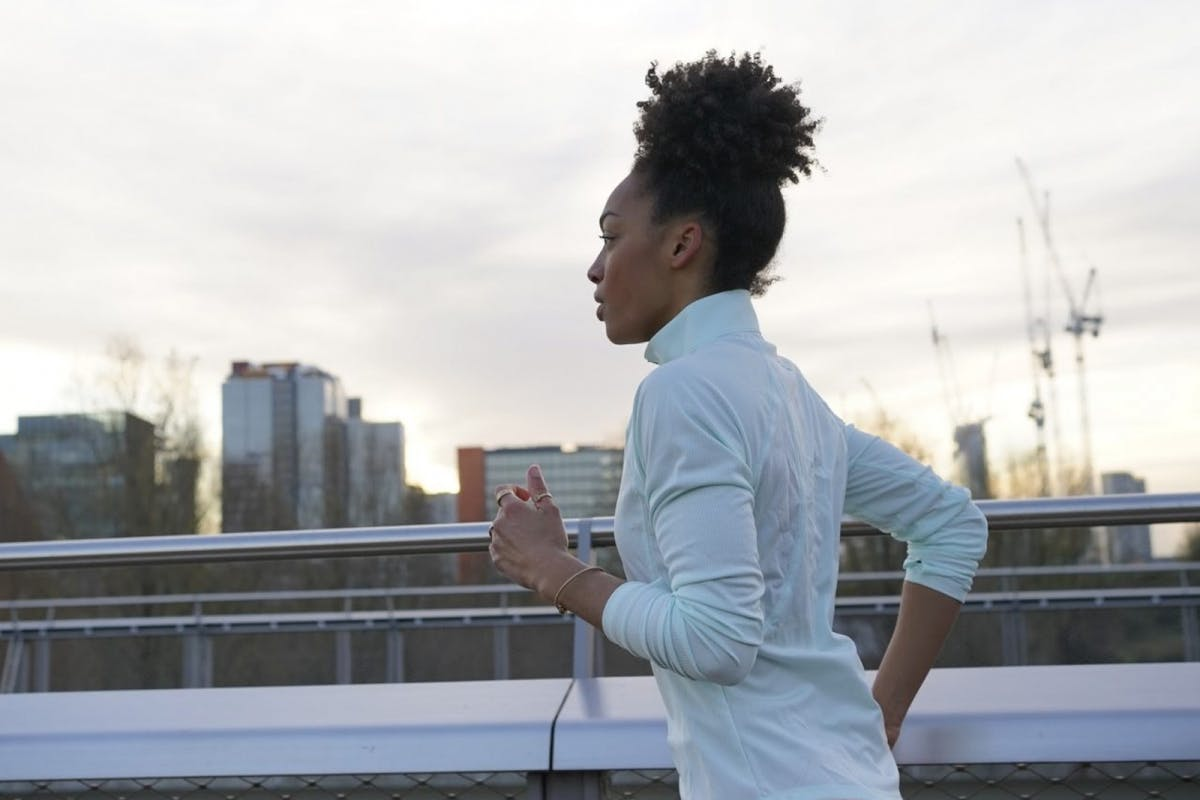 Adrienne Herbert, personal trainer and motivation coach, running outside in a white top and hair in a bun.