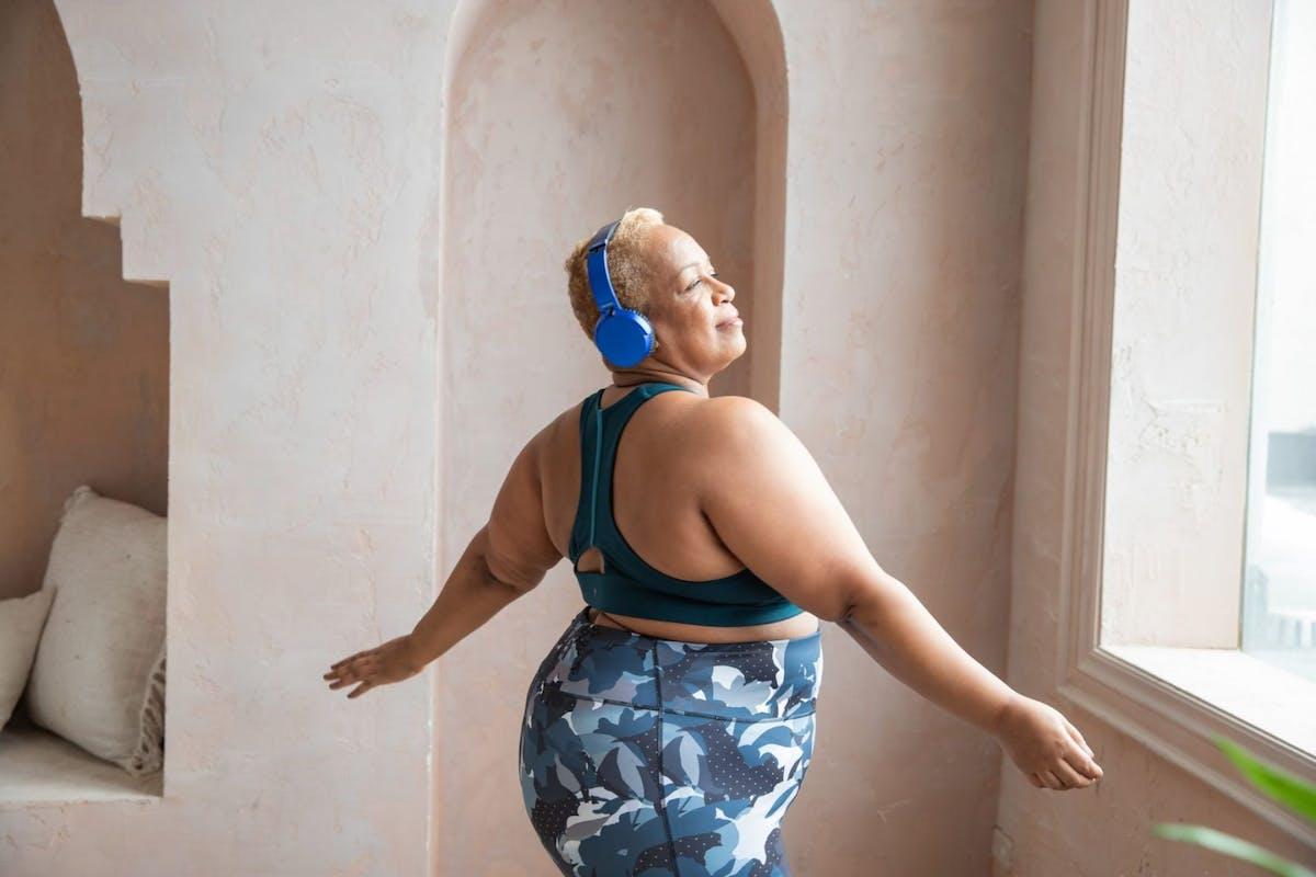 A woman dancing around her room in activewear with headphones on