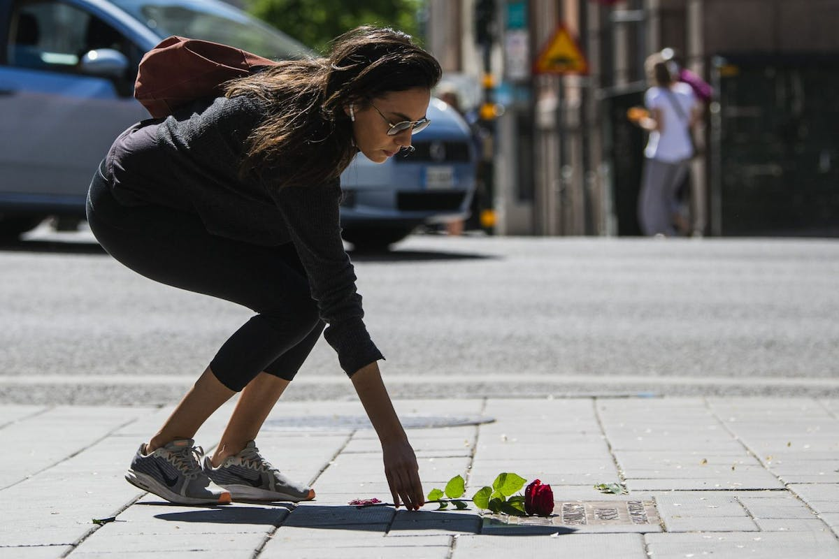 A pedestrian stops and lays a rose on June 10, 2020 at the plaque marking the site where Swedish Prime Minister Olof Palme was shot and killed on February 28, 1986 in the centrr of Stockholm.