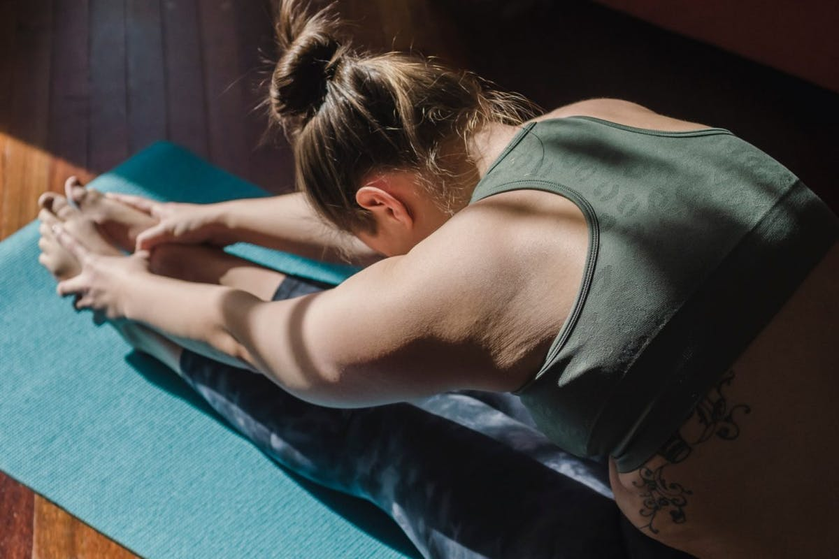 A woman doing yoga and stretching her legs out at home on a blue yoga mat