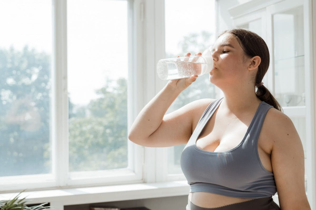 A woman taking a sip of water during a workout