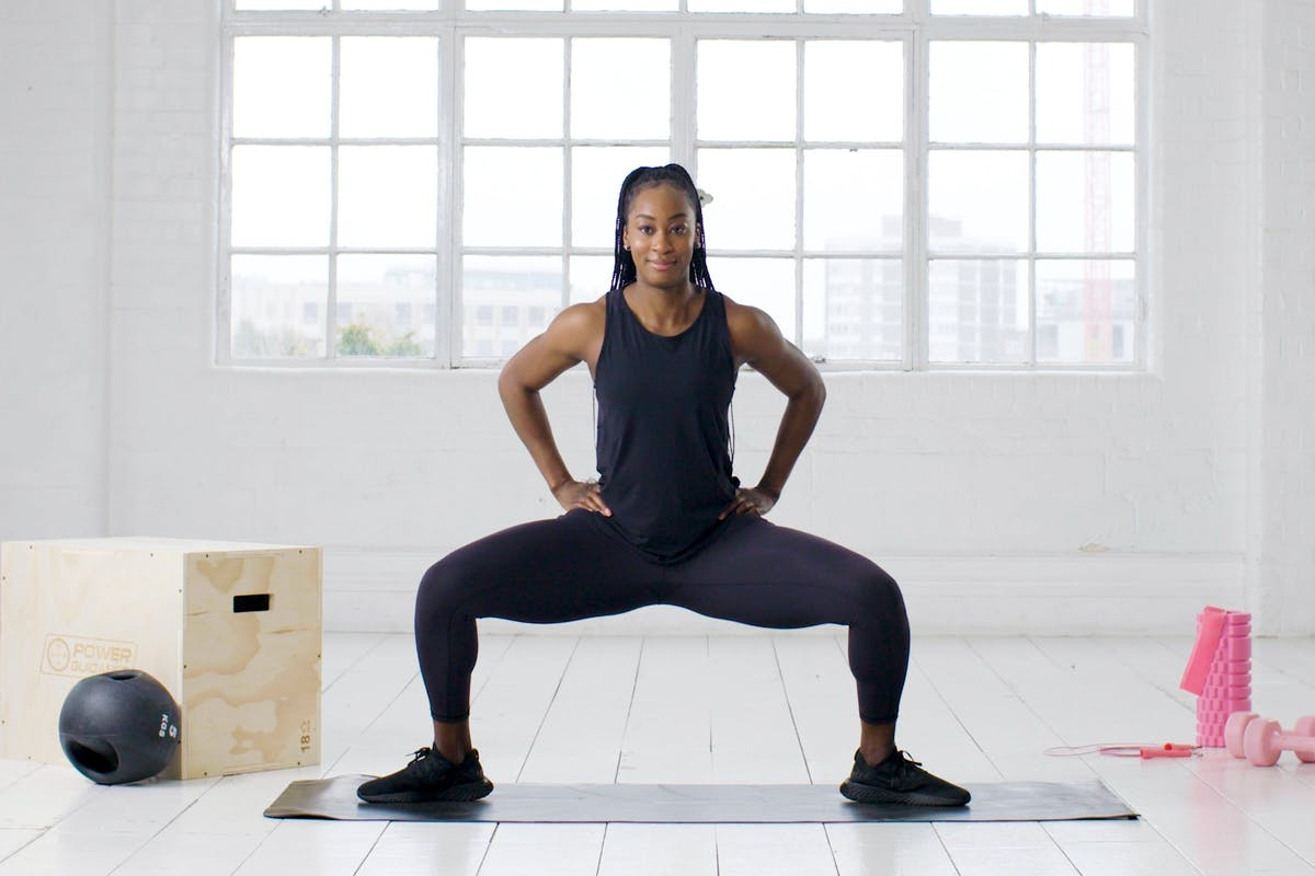 woman squatting while exercising on mat