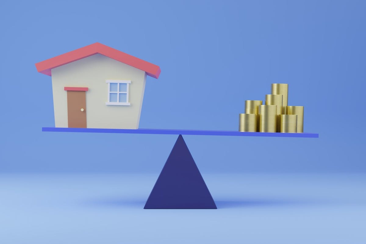 A house and a pile of money balancing on scales