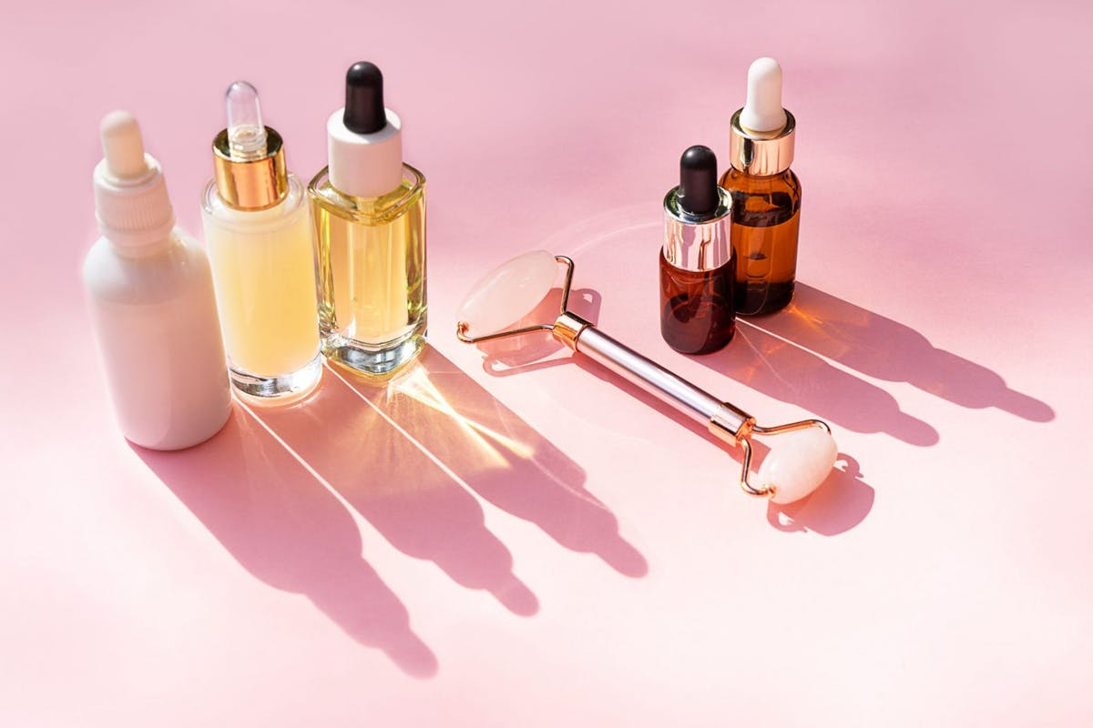A collection of skincare products on a pink background