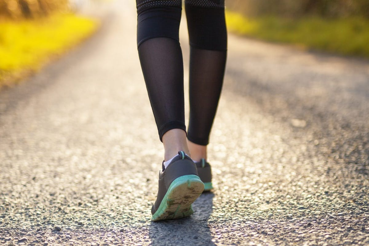 Woman walking wearing running shoes and leggings