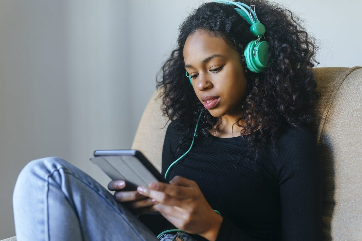 A woman listening to a podcast with headphones on at home