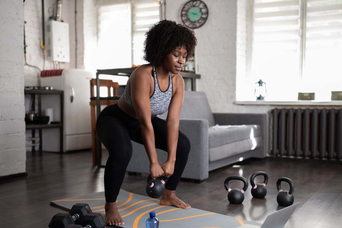 woman doing squatting exercise while holding a dumbbell