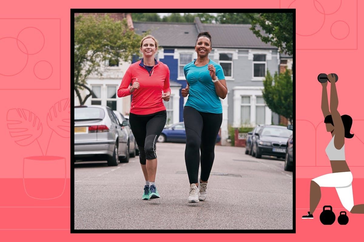 Two women jog in the middle of the road in activewear.