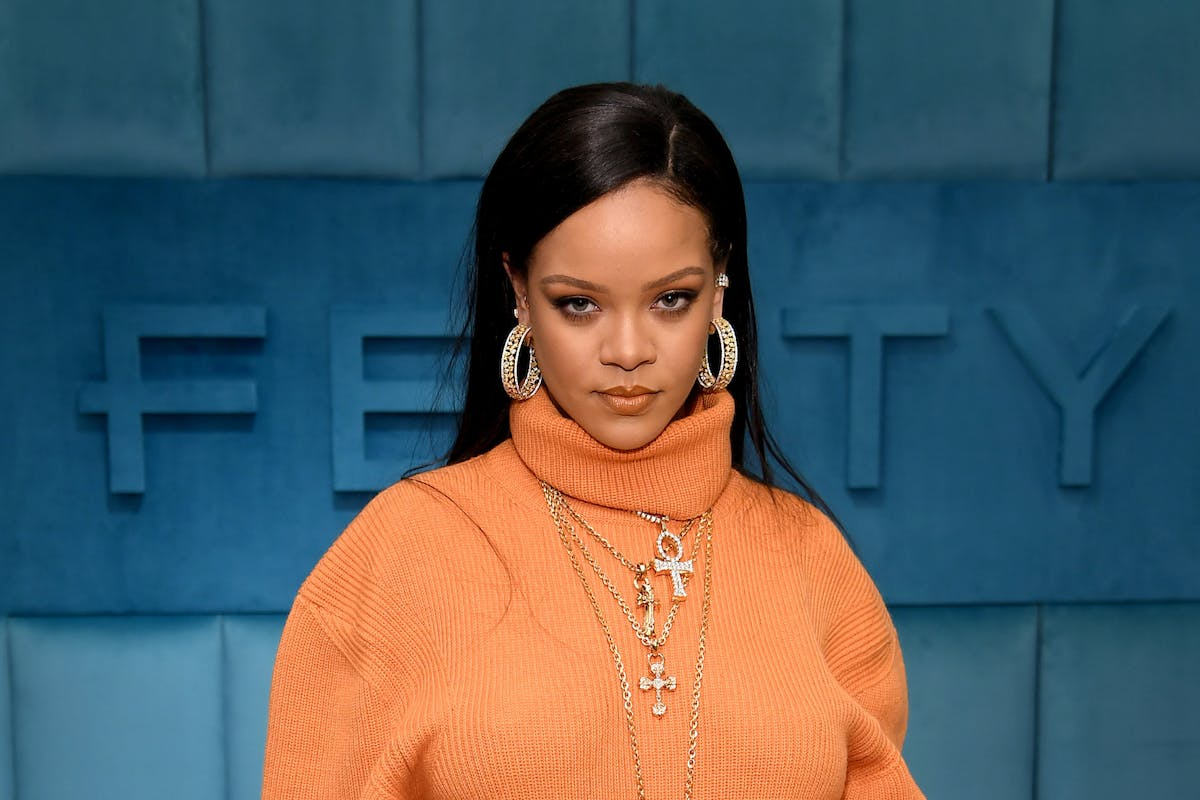 Rihanna standing in front of a Fenty sign