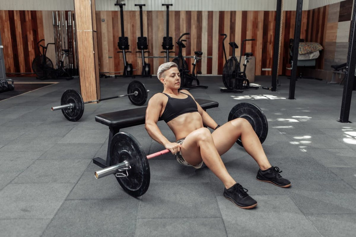 A woman doing a hip thrust in a home gym with a barbell across her hips and her back resting against a bench.
