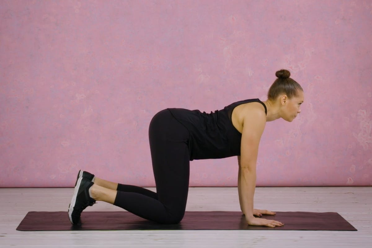 Emma OBayuvana demonstrates the cat/cow pose as part of a daily mobility challenge.