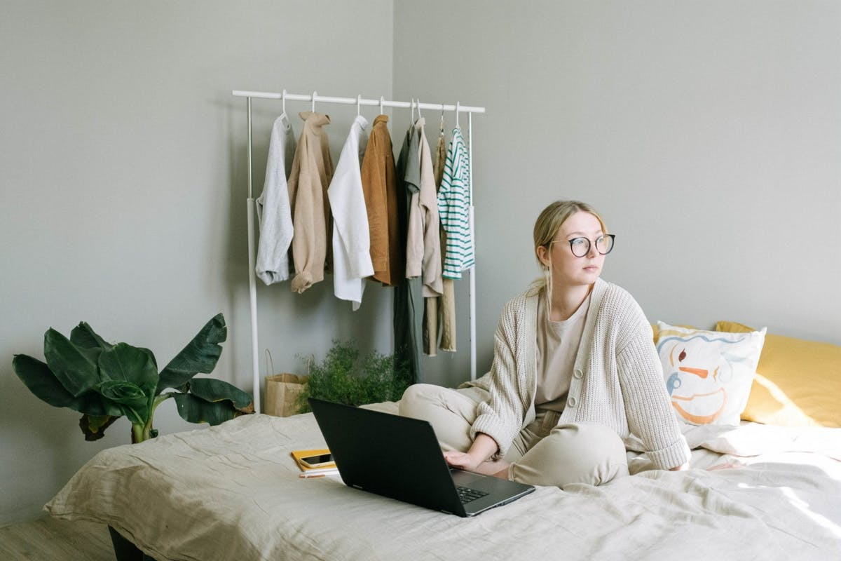 A woman sat on her bed with her laptop while working from home.