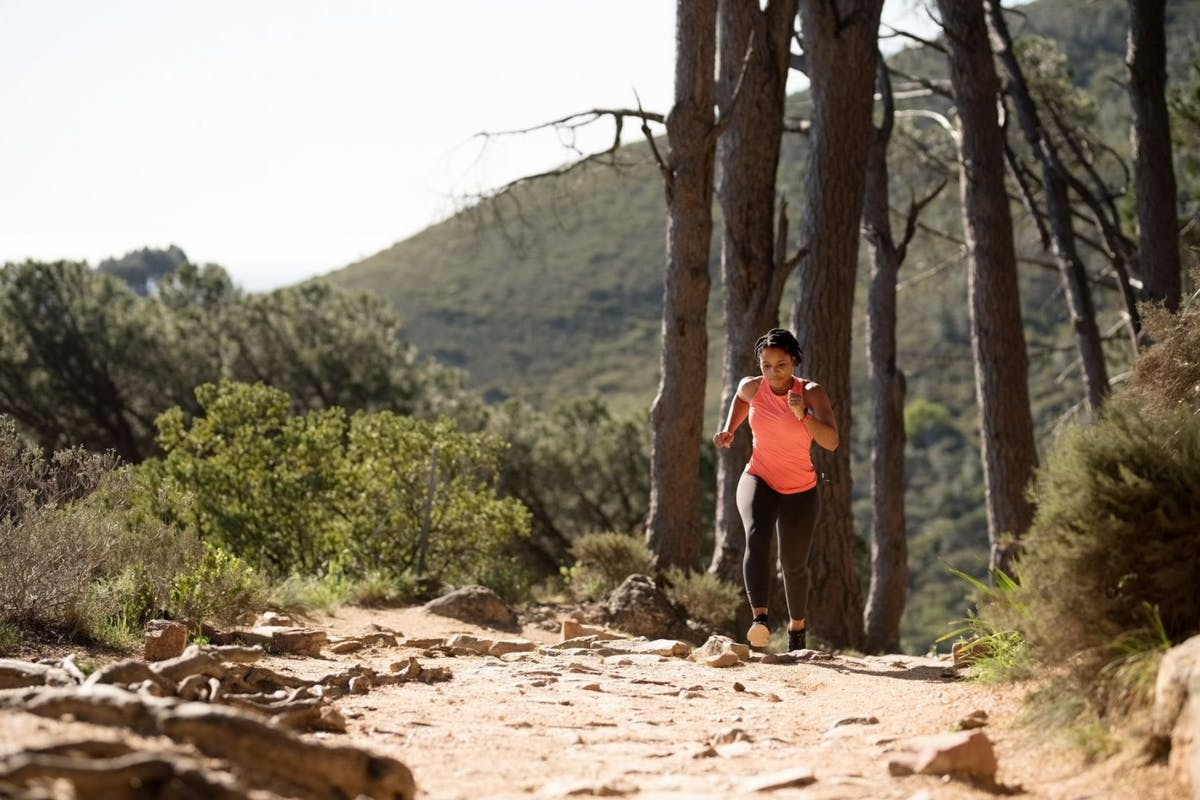 A woman in black leggings and a pink vest top running through the woodland