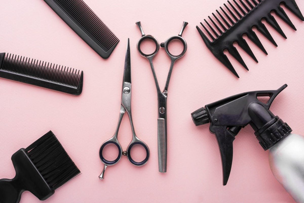 Hair tools, including scissors, combs and clippers on a pink background