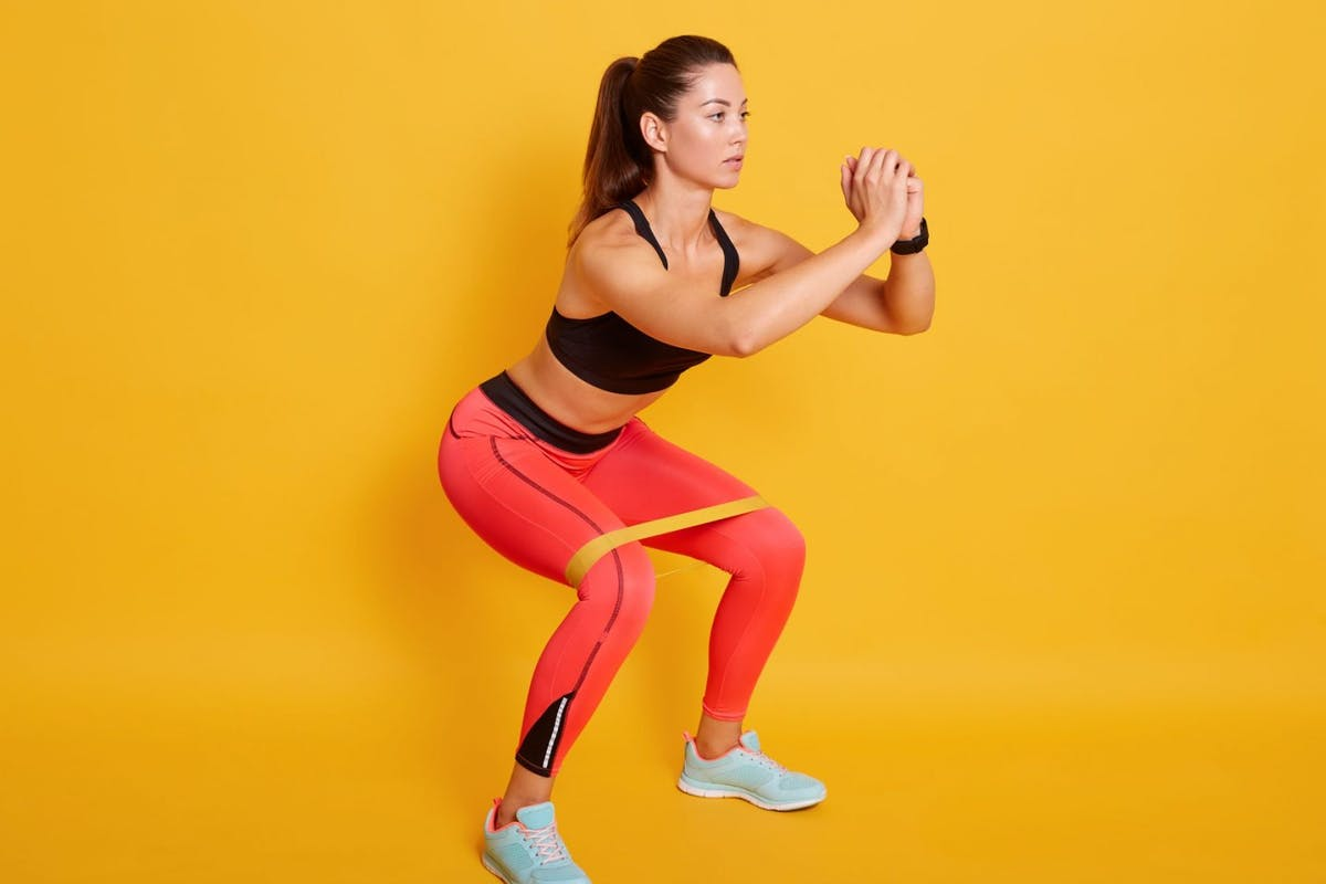 sporty woman squatting with resistance band