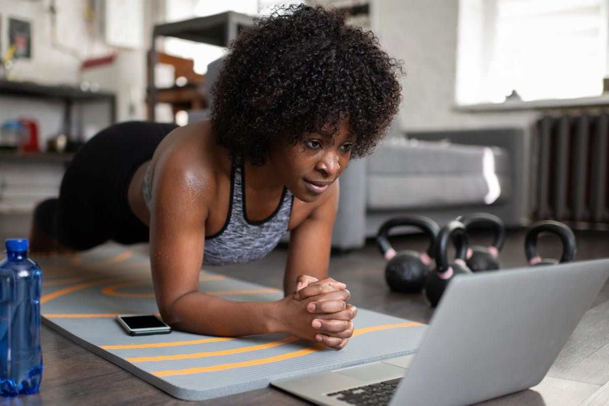 woman holding plank on a mat while working out
