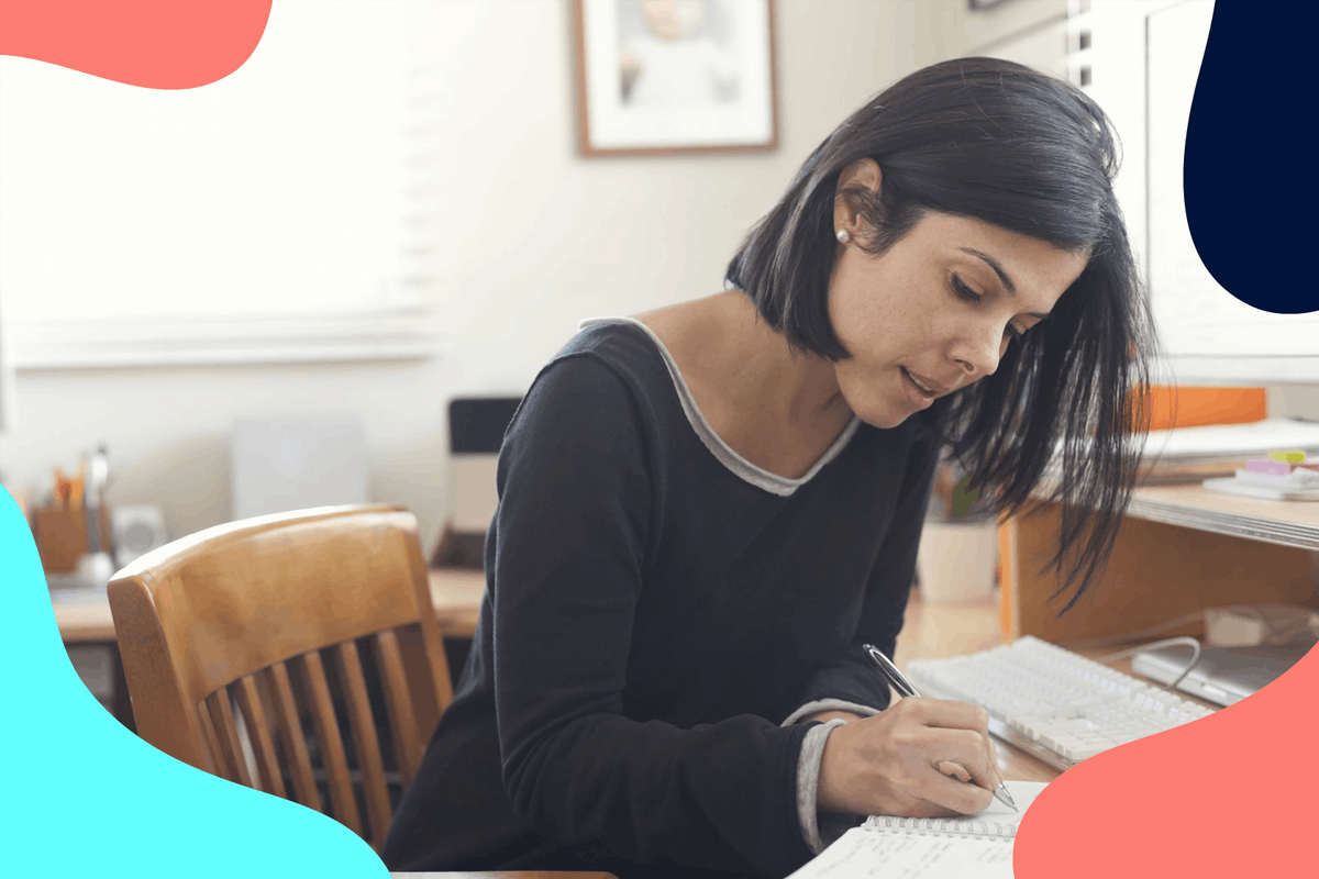 woman sat at desk writing will in notepad