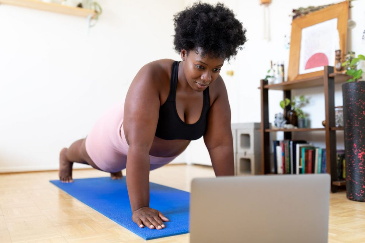 Woman doing a plank in front of a laptop