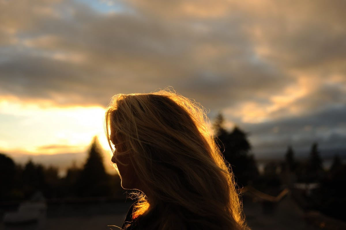 A silhouette of a woman at sunset