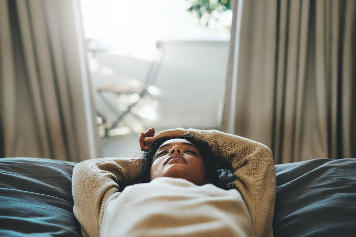 A woman lying on her bed with her eyes closed
